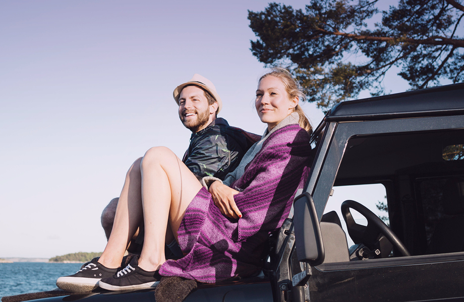 couple relaxing on top of a car